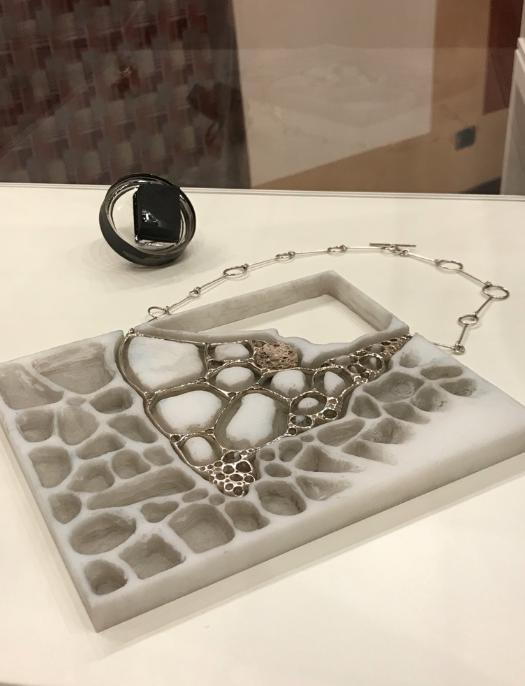 La collana scultura di Renata Manganelli e, dietro, l'anello di Sara Barbanti